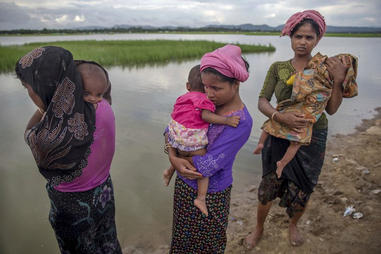 Rohingya women carry their children in the refugee camp where they are housed. Photo: Twitter/@Genocide_Report.