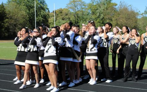 The cheerleaders teach and lead a cheer to the crowd.