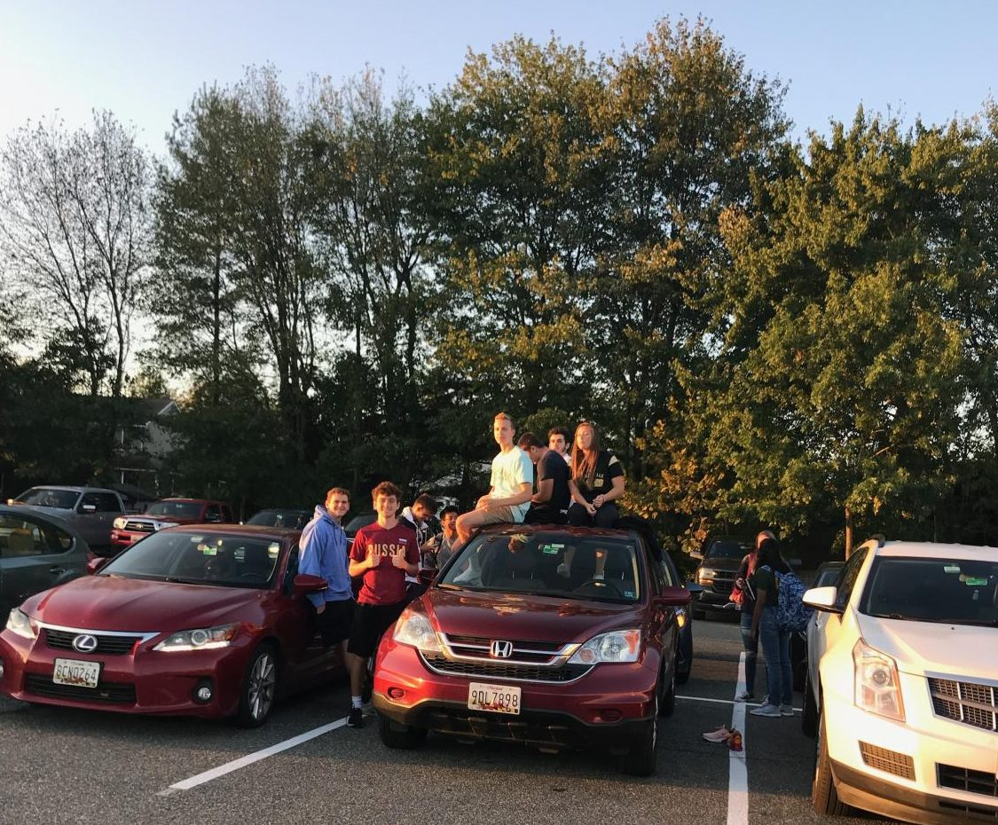 Students perch atop their cars during the Senior Sunrise.