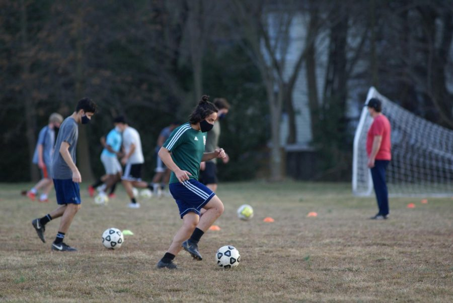 Boys' soccer warms-up with a dribbling drill at practice.