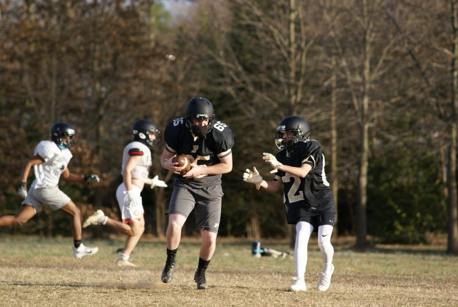 The football team runs a play in preparation for their competitions in the abbreviated fall sports season.